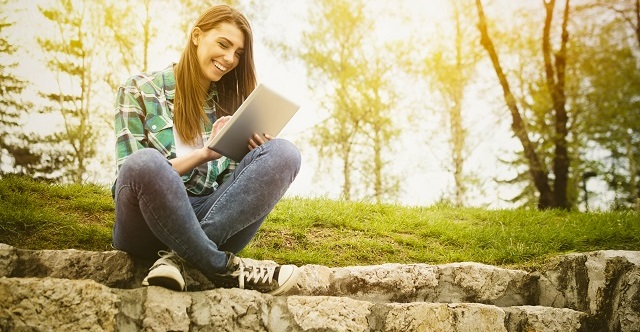 Happy young woman with digital tablet sitting in park
